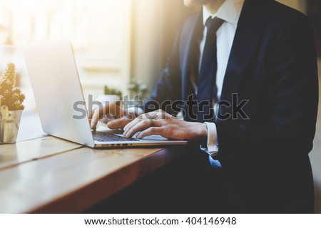 Male hands using laptop in modern coffee shop or loft, professional businessman in black suit working on new project with notebook computer while sitting at his office, flare light, blurred background - stock photo
