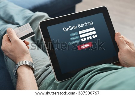 Male hands using online banking on touch screen device