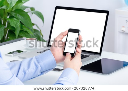 Male hands using smartphone mockup with blank screen at the office desk with an open laptop mockup and tablet computer. All devices in full focus. For responsive design presentation. - stock photo