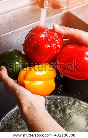 Male hands wash bell pepper. Green and yellow paprika. Fresh and juicy vegetables. Healthy lifestyle always includes diet. - stock photo