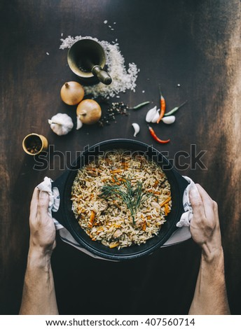 Male hands with bowl of fried rice with pork over the aged wooden table. Top view. Vintage style - stock photo