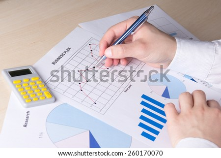 male hands with pen and business report on table - stock photo