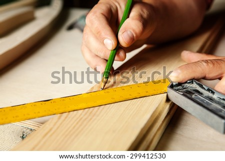 Male hands with ruler and pencil closeup. Professional carpenter at work. - stock photo