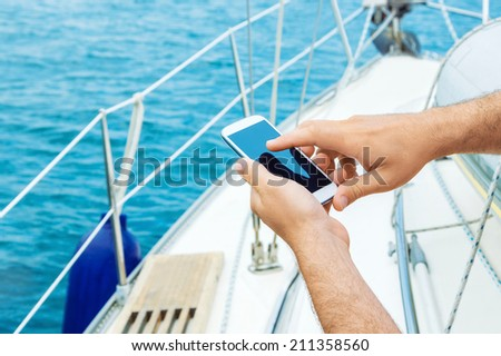 Male hands with smartphone on sailing  - stock photo