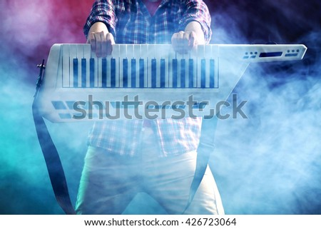 Male hands with synthesizer in smoke - stock photo