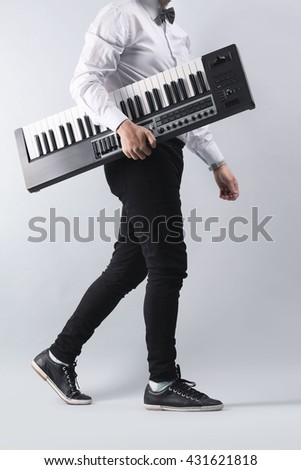 Male hands with synthesizer on light wall background - stock photo