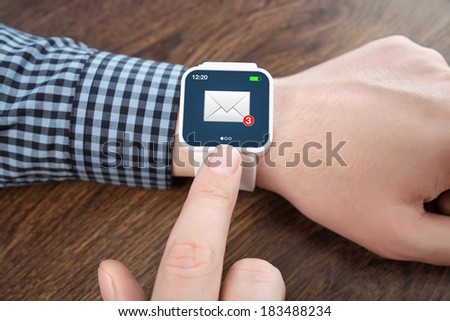 male hands with white smartwatch with email on the screen over a wooden table in an office - stock photo