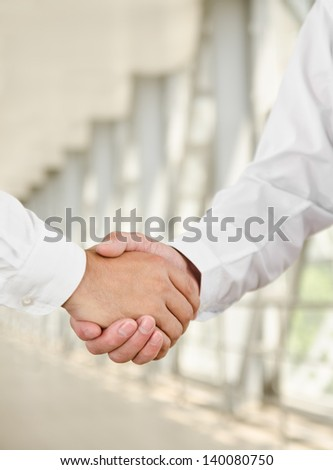 Male handshake isolated on business background - stock photo