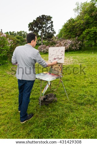 Male handsome artist during creation a sketch of his picture on a trestle and easel painting with oils and acrylics in a garden - stock photo
