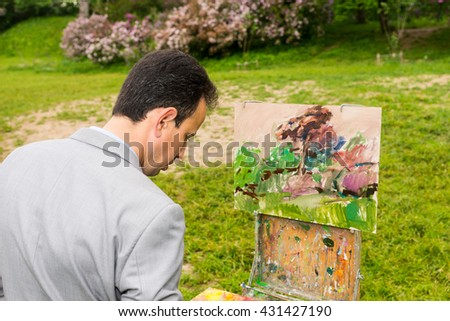 Male handsome middle-aged creative artist  standing in front of a sketchbook during an art class in a outdoors - stock photo
