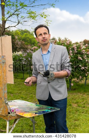 Male handsome middle-aged dreamy artist working  on a trestle and easel painting with oils and acrylics during an art class in a park - stock photo