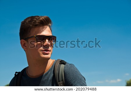 male handsome model in sunglasses on blue sky background