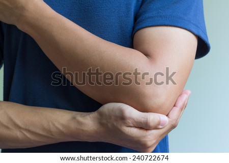 male having pain in injured arm - stock photo
