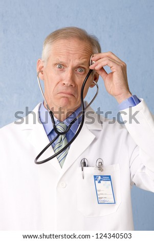 Male health care professional looking to the camera concerned and bewildered with stethoscope and medical identification card three quarter view on blue background