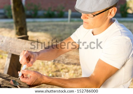 Male heroin abuser preparing to take an injectable drug dose, outdoors - stock photo