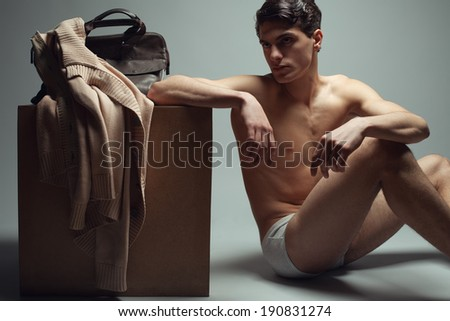 Male high fashion concept. Portrait of a handsome male model sitting near a wooden cube in trendy underwear. Cardigan and leather bag on a cube. Perfect skin & haircut. Vogue style. Studio shot - stock photo