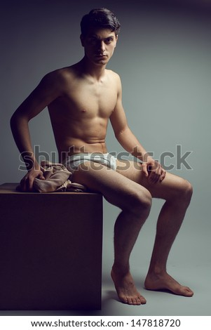 Male high fashion concept. Portrait of a handsome male model sitting on a wooden cube in stylish underwear. Perfect skin & haircut. Vogue style. Copy-space. Studio shot
