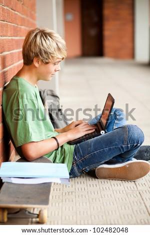 male high school student using laptop in school - stock photo