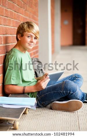 male high school teen student using tablet computer in school - stock photo
