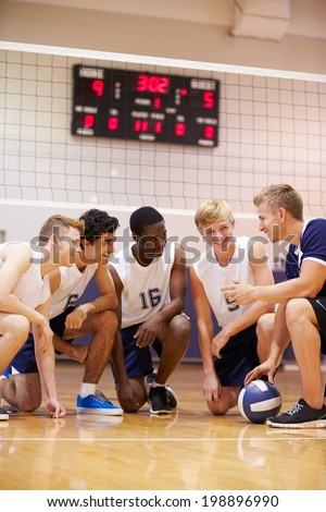 Male High School Volleyball Team Having Team Talk From Coach - stock photo