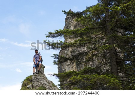 Male hiker on the top of a mountain in summer - stock photo