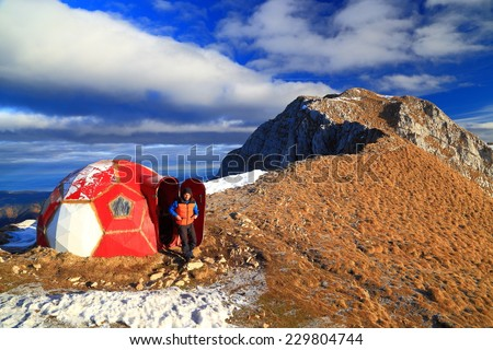 Male hiker opens the door of red refuge on the mountain  - stock photo