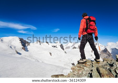 Male hiker standing in front of Monte Rosa Glacier during an high altitude hiking. Switzerland, Europe. - stock photo