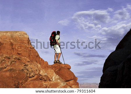 Male hiker standing on red rocks looking at view.