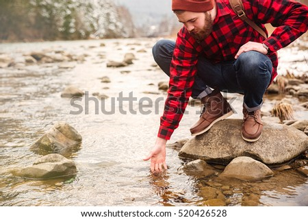Male hiker testing water in the river