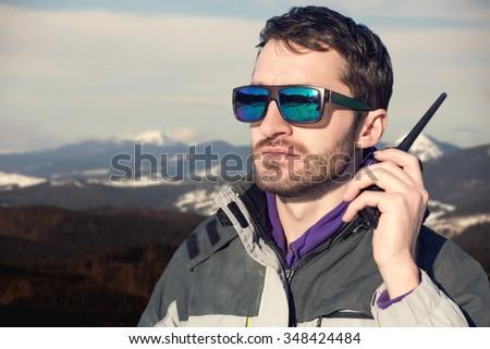 Male hiker using walkie talkie against mountain peaks. - stock photo