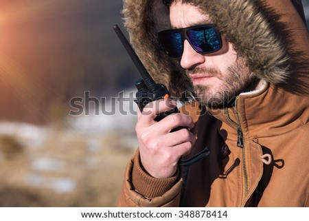 Male hiker using walkie talkie against mountain peaks. - stock photo