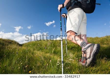 Male hiker walking along a mountain path. Horizontal orientation. Low angle view - stock photo