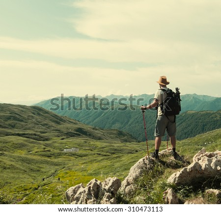 Male hiker with backpack looks into the distance.