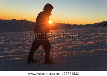 Male hiker with walking sticks on top of mountain