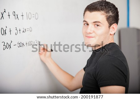 Male Hispanic high school student solving some math problems on a white board at school