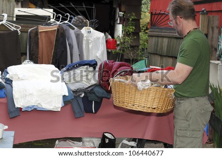 Male holding a basket with linens inside at a yard sale in front of a table with a sleeping bag and clothing items.