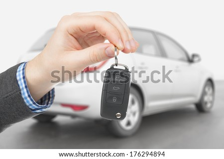 Male holding car keys with car on background - stock photo