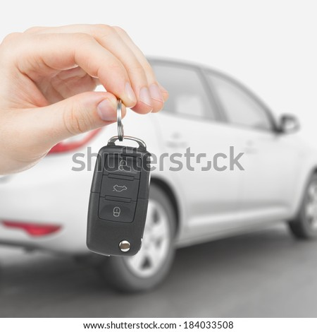 Male holding car keys with car on background - 1 to 1 ratio - stock photo