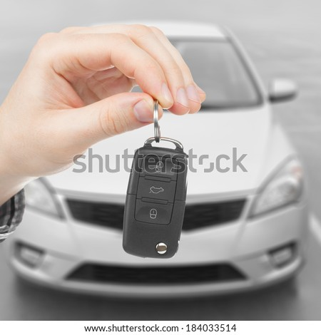 Male holding car keys with parked car on background - 1 to 1 ratio - stock photo