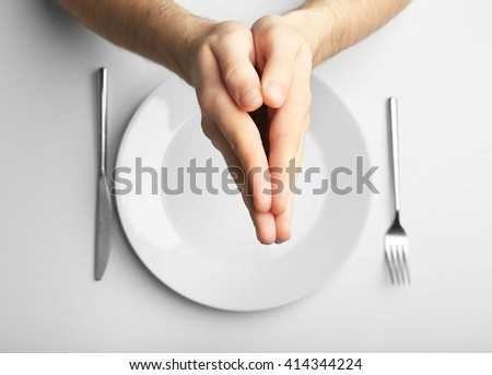 Male holding hands together over plate, isolated on white - stock photo