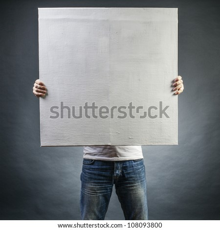 male holds a square canvas primed - stock photo