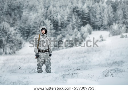 Male hunter in camouflage, armed with a rifle, standing in a snowy winter forest