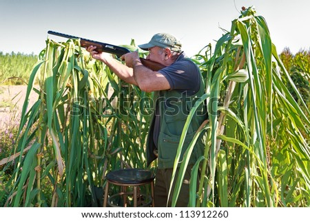 Male hunter in the field aiming the hunting rifle during a hunt. - stock photo