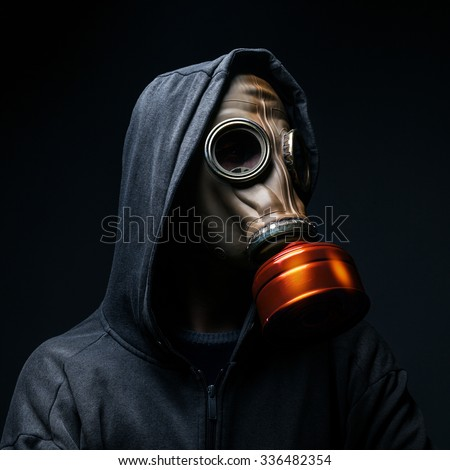 male in a gas mask on a dark background - stock photo