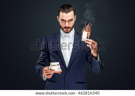 Male in a suit holding burning cash and bank card. isolated on grey background.