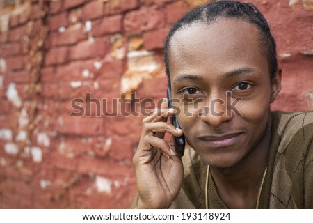 Male in front of red brick wall on phone - stock photo