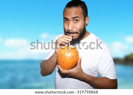 male in holiday drinking coconut water - stock photo