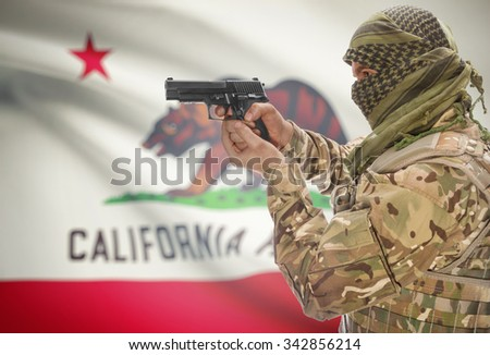 Male in muslim keffiyeh with gun in hand and flag on background series - California - stock photo