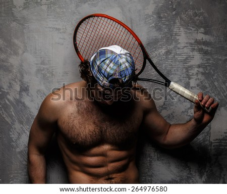 Male in white shorts with tennis racket over grey wall.
