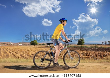 Male in yellow shirt riding a mountain bike on a sunny day, Macedonia - stock photo